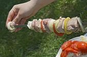 stock photo of impaler  - Hand impaling meat on a skewer for a shashlik - JPG