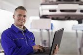 Smiling mechanic using a laptop in a garage