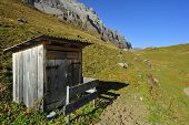foto of outhouses  - A small wooden outhouse standing isolated hight in the Swiss alps - JPG