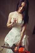 pic of gory  - Sexy bloody bride with chainsaw and chamomile in empty room - JPG