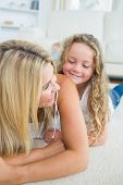 Smiling daughter tickling her mother on living room floor