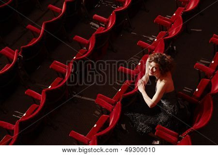 Portrait of a smiling young woman sitting in theatre stall