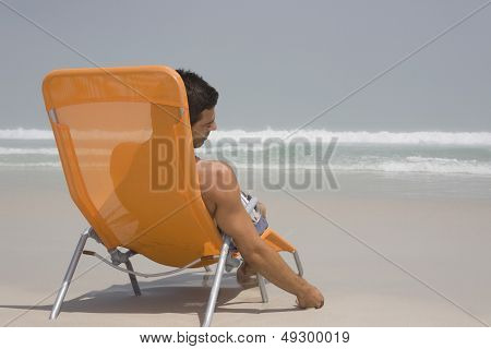 Rear view of a man sitting on deckchair at beach