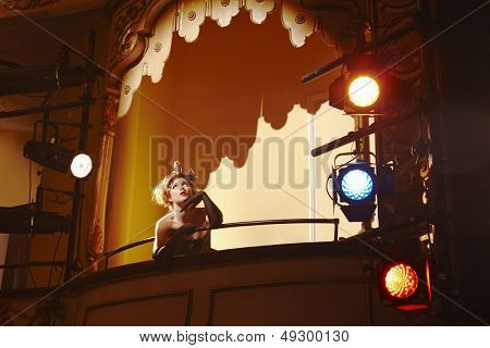 Low angle view of a beautiful young woman in theatre box