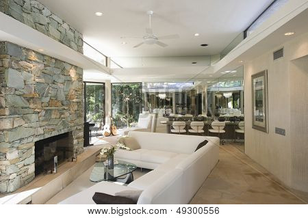 Sunken seating area and stone fireplace with dining area in background at home