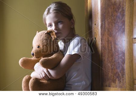 Closeup side view of a little girl embracing her teddy bear