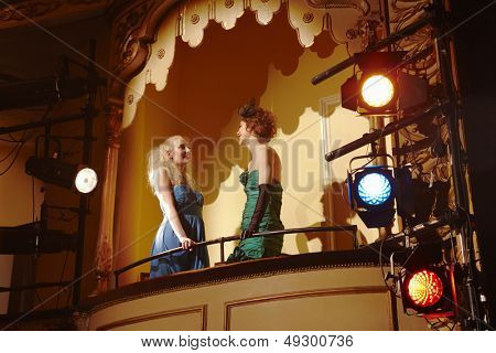 Low angle view of two young women talking in theatre box
