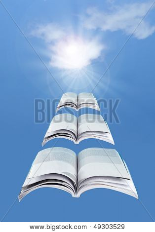 Flying open books over a blue sky