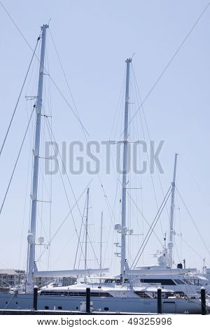 The masts of large luxury yachts docked at a marina in Florida.