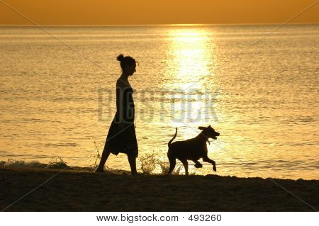Woman With Dog At Sunset