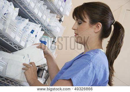 Female nurse standing at shelf with medicinal supplies