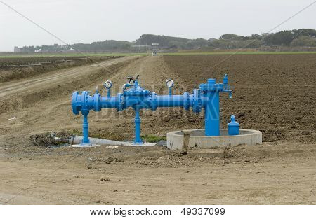 Blue irrigation pipes on barren ground