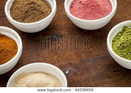 super fruit and leaf powders in small ceramic bowls with copy space - baobab, nori, yumberry, moringa, mangosteen
