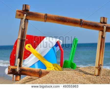 Children's Toys And Santa's Hat  In Bamboo Frame On The Beach