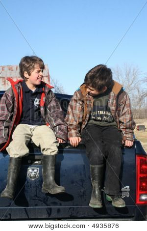 Two Boys Sitting On A Truck