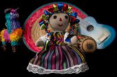 stock photo of pinata  - Mexican doll pinata guitar hat and maracas isolated on black background - JPG