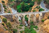 picture of tar  - Arched road bridge with high stone arches crossing a river bed in mountainous countryside with tarred roads - JPG