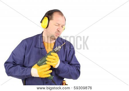 Worker in ear muffs with drill