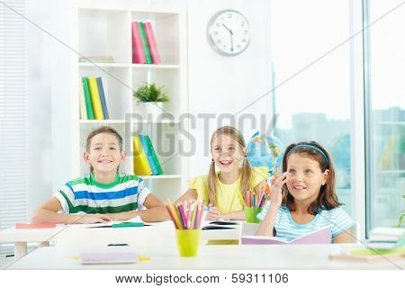 Portrait of joyful schoolmates looking at something attentively at lesson