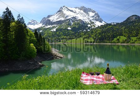 Wine and vegetables served at a picnic in Alpine meadow. Switzerland