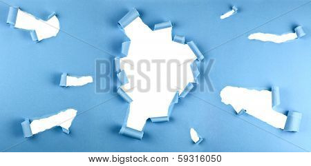 Group of torn holes in blue paper isolated over a white background