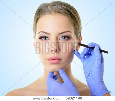 Beautiful woman ready for cosmetic surgery, female face with doctor's hands with pencil, over blue