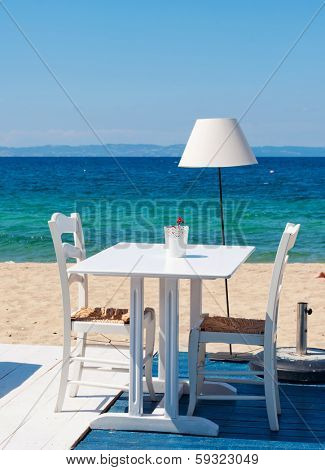 Two chairs and table from restaurant on the beach and horizon over sea in the background