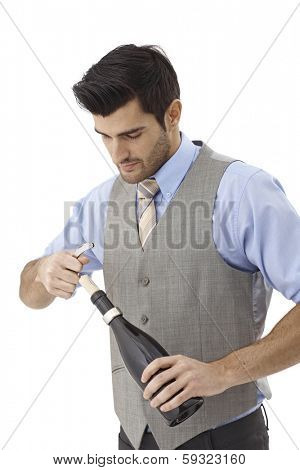 Male wine-expert opening bottle of wine by screw driver.