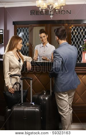 Receptionist giving information to guests upon arrival at hotel.