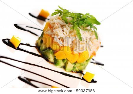 Salad with crab meat, mango and avocado on a white plate.