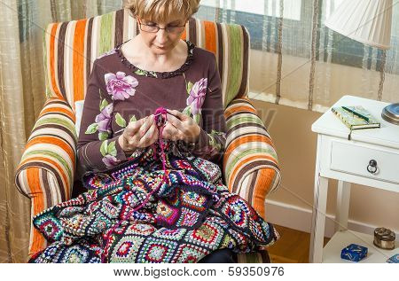 Portrait of woman knitting a vintage wool quilt