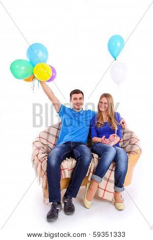 Young Couple Sitting On A Sofa With Balloons