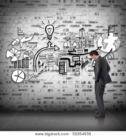 Businessman with hands on hips against brainstorm on the wall