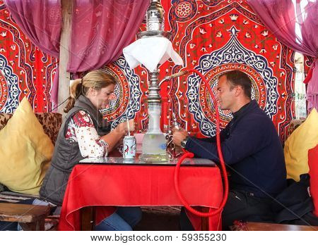 DAHAB, EGYPT - JANUARY 24, 2011: Couple sitting in the oriental bar with nargile at table. These water-pipes allow you to smoke flavoured tobacco as it is bubbled through water.