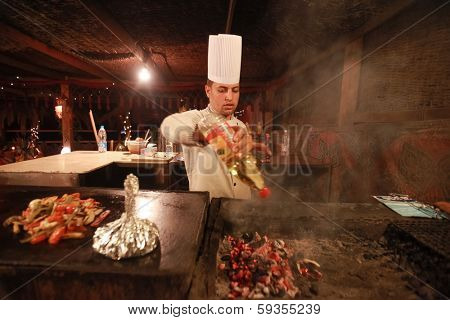DAHAB, EGYPT - JANUARY 28, 2011: Egyptian cook prepares traditional meal. Egyptian food is a mixture of all the different civilisations that came to Egypt in the history of its existence.