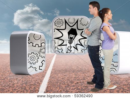 Young couple standing back to back against track with sky in background