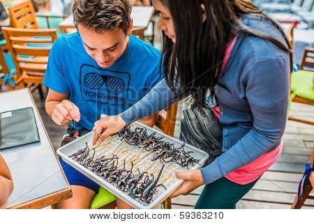 Bangkok, Thailand - December 30, 2013: tourist eating scorpion skewers
