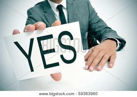 man wearing a suit sitting in a table showing a signboard with the word yes written in it
