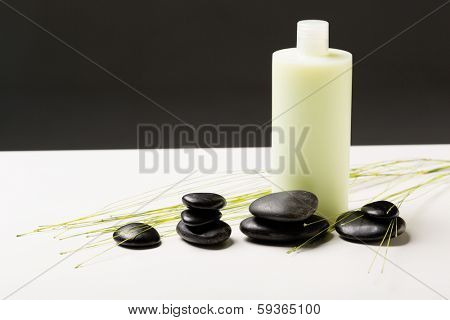 spa, health and beauty concept - closeup of shampoo bottle, massage stones and green plant