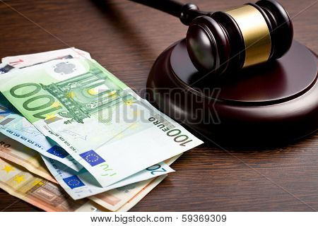 judge gavel with euro bills on wooden background