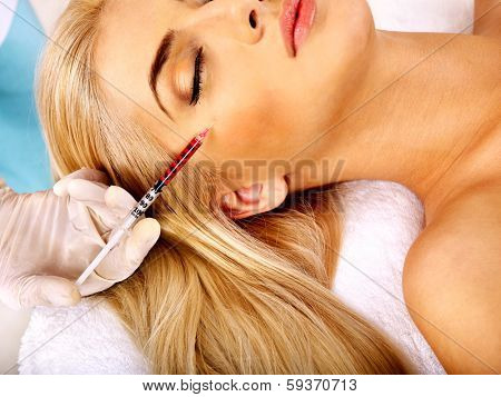 Beauty woman giving facial injections.