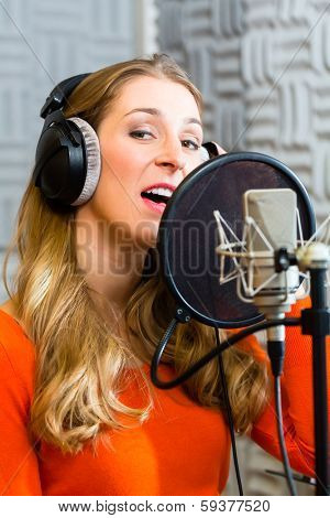 Young female singer or musician with microphone and headphone for audio recording in the Studio