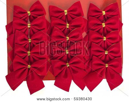 A mass of velvet like Christmas bows on a cardboard backing sheet.