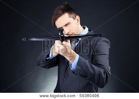 Young businessman with crossbow, on dark background
