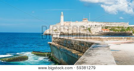 The castle of El Morro in Havana and the famous  wall of Malecon with white puffy clouds on a blue sky