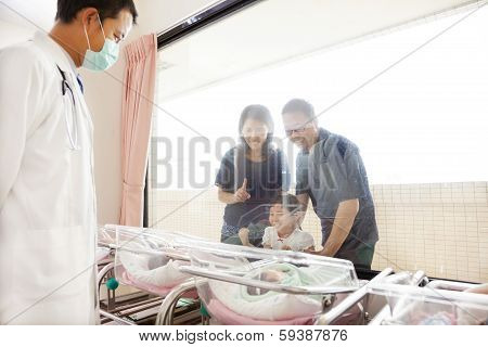 Family Watching Newborn In Childbearing Center And Doctor