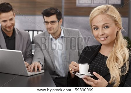 Beautiful businesswoman taking a break, drinking coffee, smiling, looking at camera, while colleagues working at background.