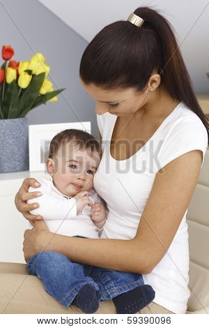 Young mother holding baby boy on lap, embracing tenderly.