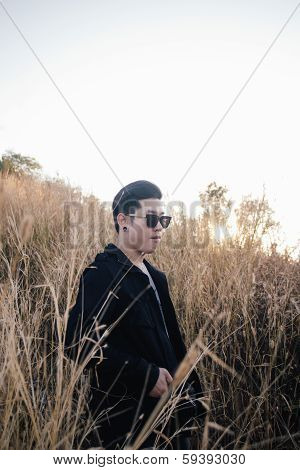 Portrait Young Man In Grass Field With Sunrise