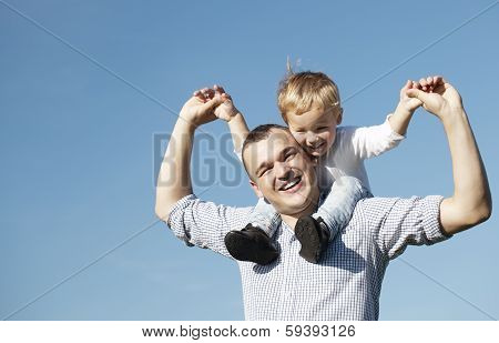 Dad giving his young son a piggy back ride